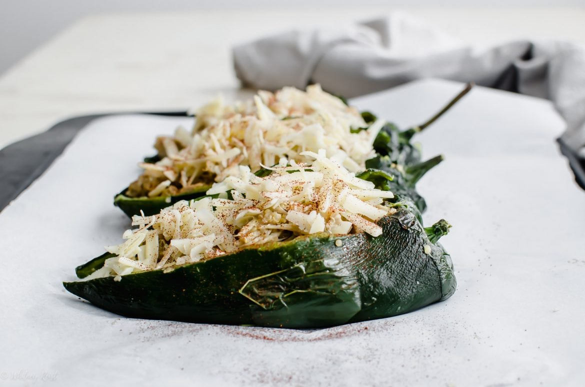 A sheet pan with unbaked stuffed poblano peppers.