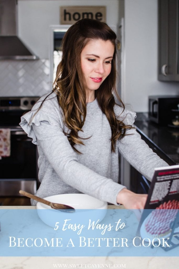 A brunette woman reading a cookbook at a white marble counter with a mixing bowl on top.