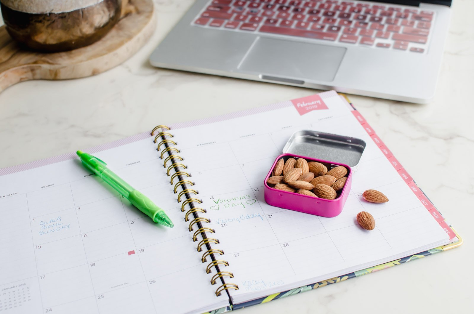 A planner set pen with a green pin and a snack tin with almonds.
