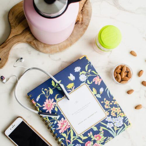 An overhead flatly shot of a water bottle, day planner, head phones, almonds, and a cell phone.