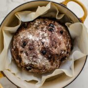 A yellow Dutch oven with a chocolate rye boule inside.
