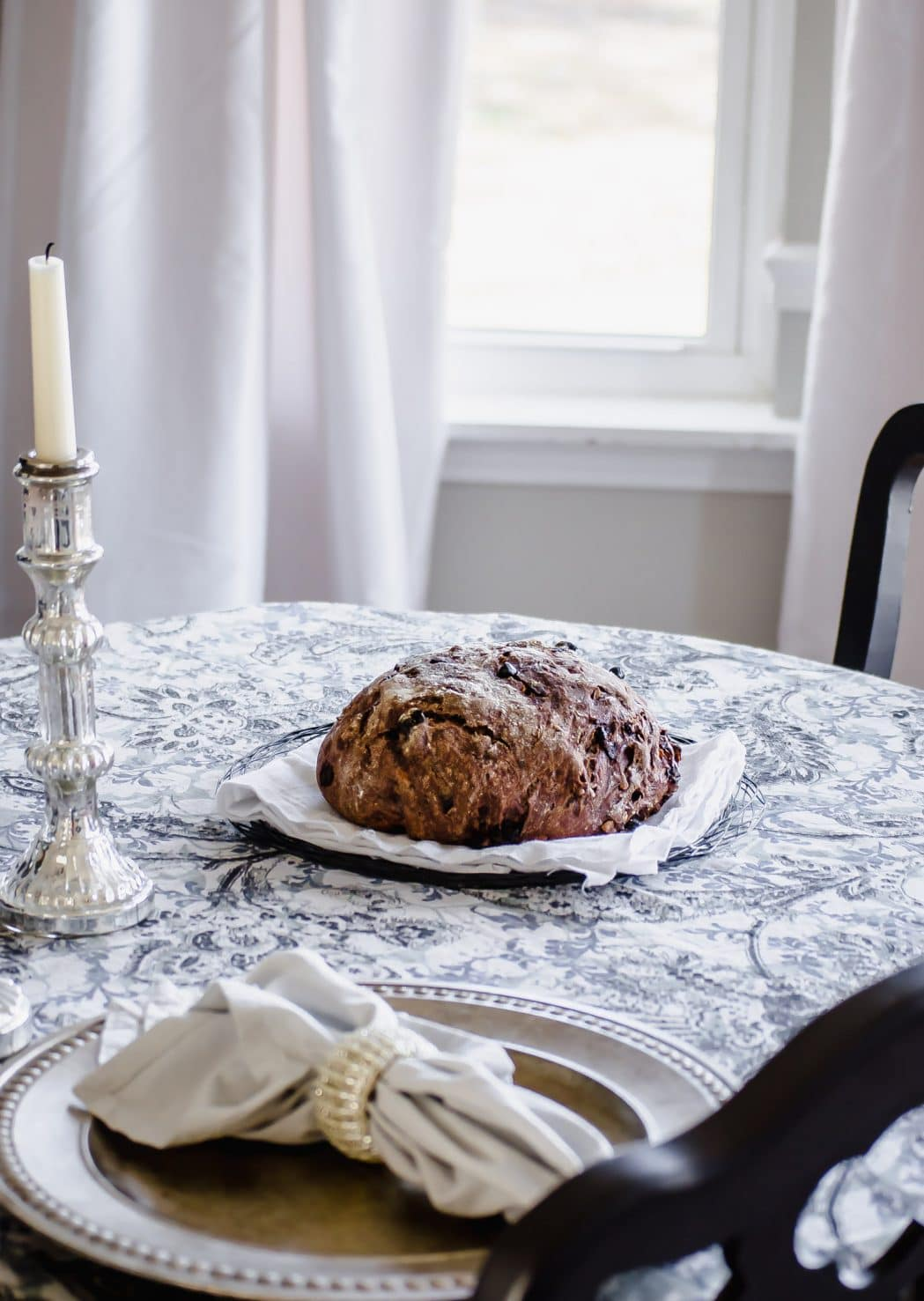 A loaf of chocolate rye bread on a table.