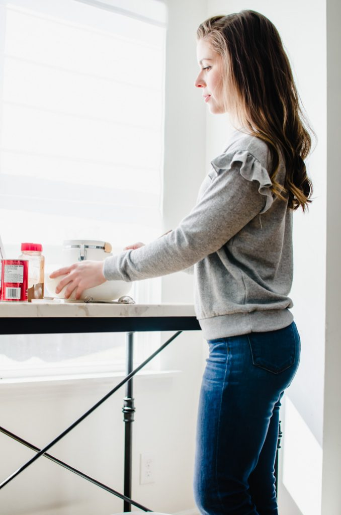 A brunette woman standing a white counter top preparing to mix in a bowl.