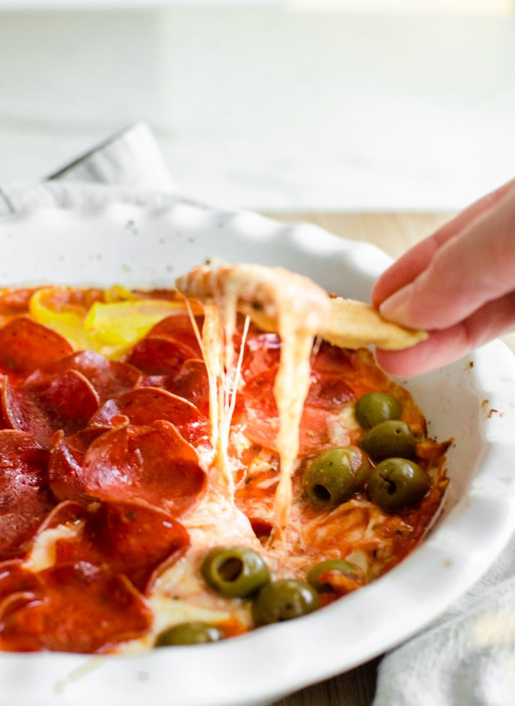 A hand with a pita chip dipping into a dish of baked pizza dip.