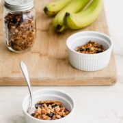 A cutting board with granola, a glass of milk, and bananas.