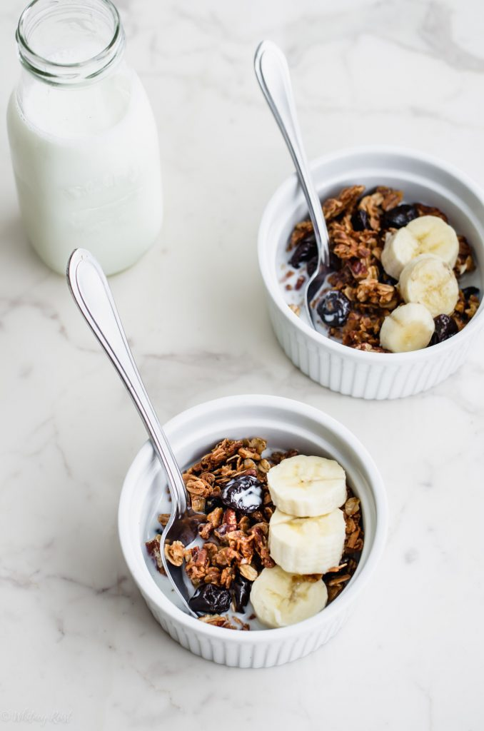 Two white bowls filled with cherry pecan granola, milk and sliced banana.