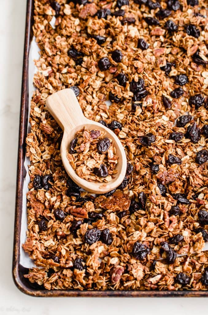 A baking sheet filled with cherry pecan granola and a wooden scoop.