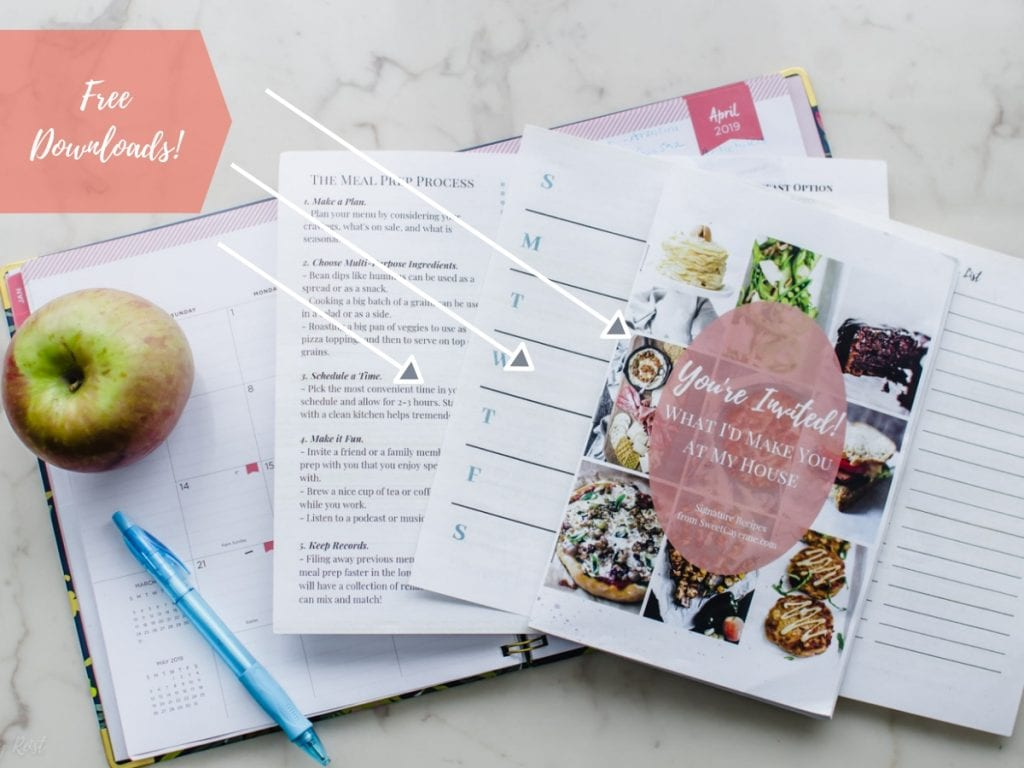 Menu planning sheets with a planner and apple on a white marble counter.