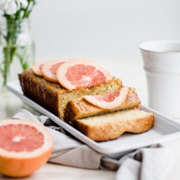 A loaf of sliced grapefruit cake on a white platter with flowers and a cup of tea on the side.