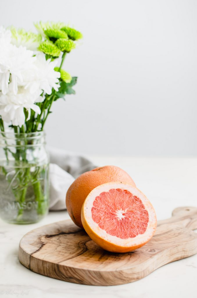 A sliced grapefruit on a cutting board with flowers on the side.