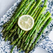 A blue and white tray with roasted asparagus and a lemon slice on top.