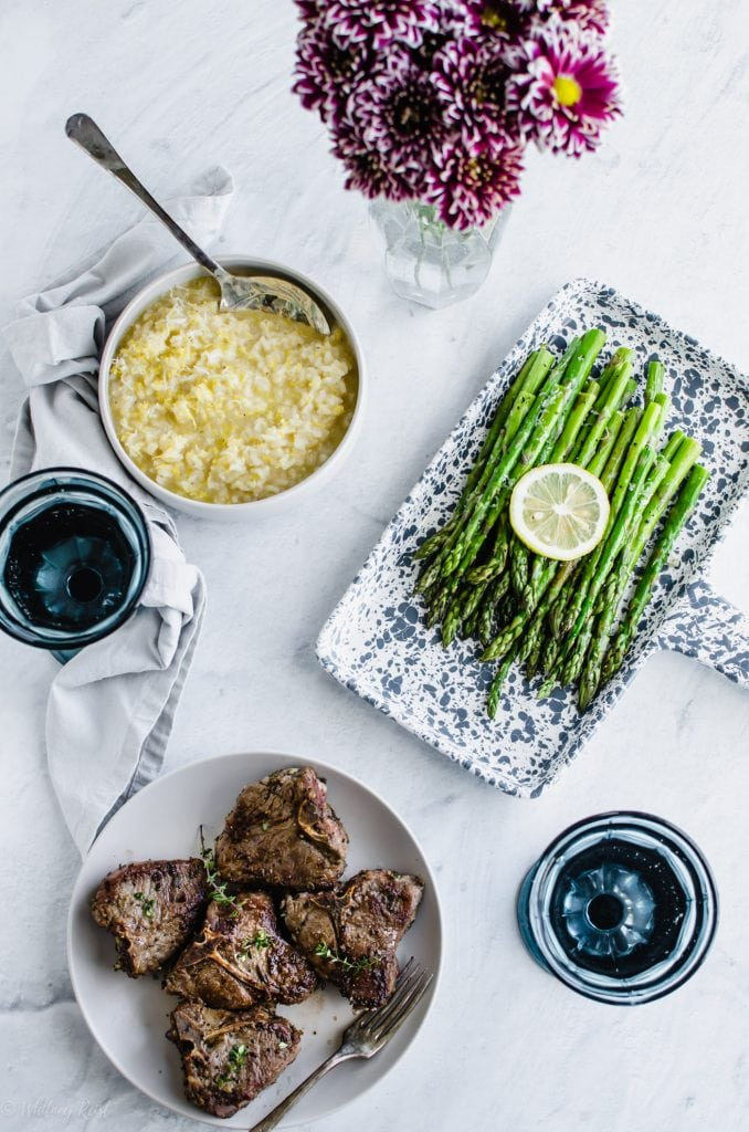 A dinner table with asparagus, risotto, and pork chops.