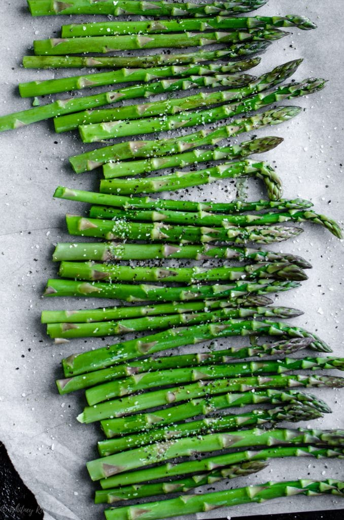A sheet pan lined with parchment paper and filled with roasted asparagus.