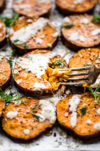 A fork slicing into a round of roasted sesame sweet potatoes on a baking sheet.