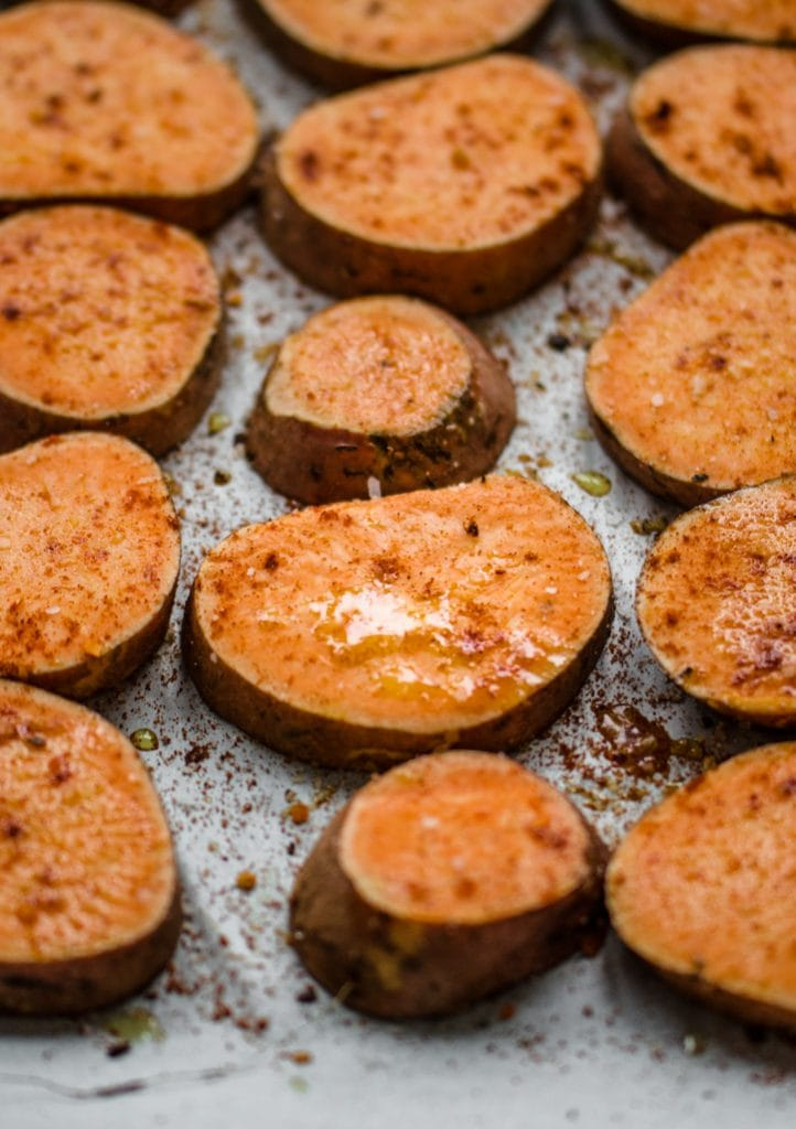 Round pieces of sweet potato on a baking sheet sprinkled with spices and olive oil.