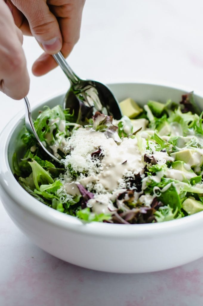 A white bowl filled with springtime everyday salad with hands and utensils tossing the salad.