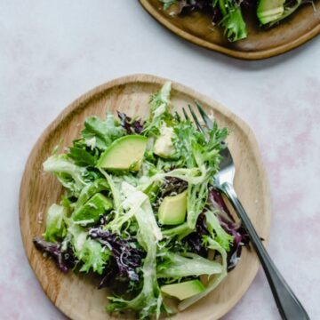 An overhead shot of wooden plates with springtime everyday salad on top.