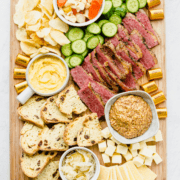 A St. Patrick's day themed snack board with corned beef, sauerkraut, soda bread, and other charcuterie items.