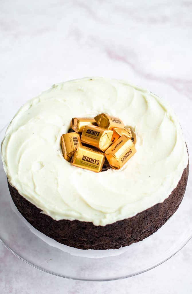 A chocolate cake with cream cheese frosting and a Hershey's gold nuggets in the center.