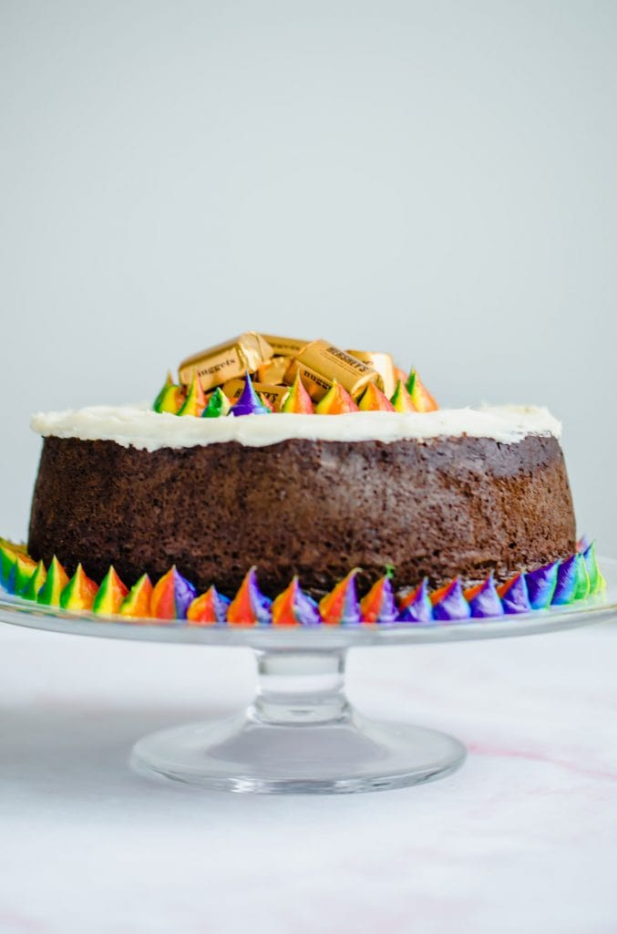 A shot of a Pot O' Gold Chocolate Stout Cake on a glass cake stand.