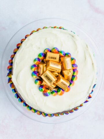 An overhead shot of a Pot O' Gold chocolate stout cake on a pink marble backdrop.