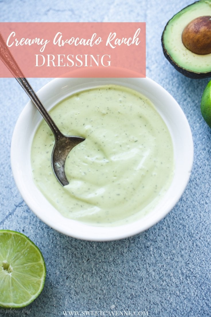A white bowl filled with creamy avocado ranch dressing on a blue stone counter with limes on the side.