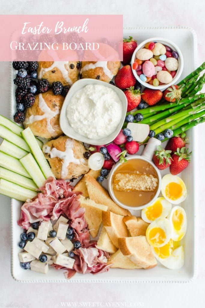 A white rectangle platter filled with items for an Easter brunch grazing board against a pink marble background.
