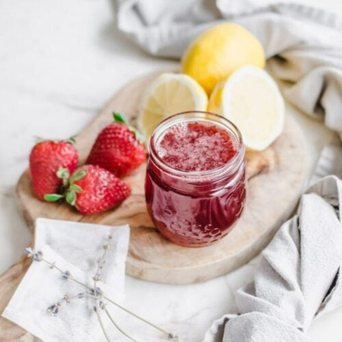 A jar of strawberry lavender syrup on a cutting board with lemons and strawberries on the side.