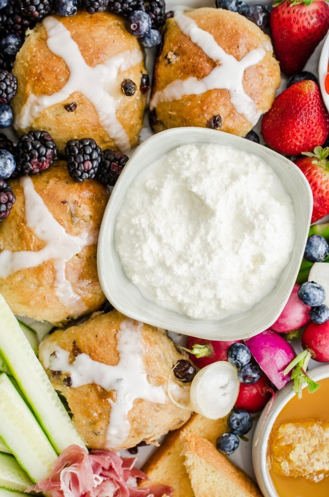 A close up shot of a bowl of fresh ricotta cheese on an Easter brunch grazing board.