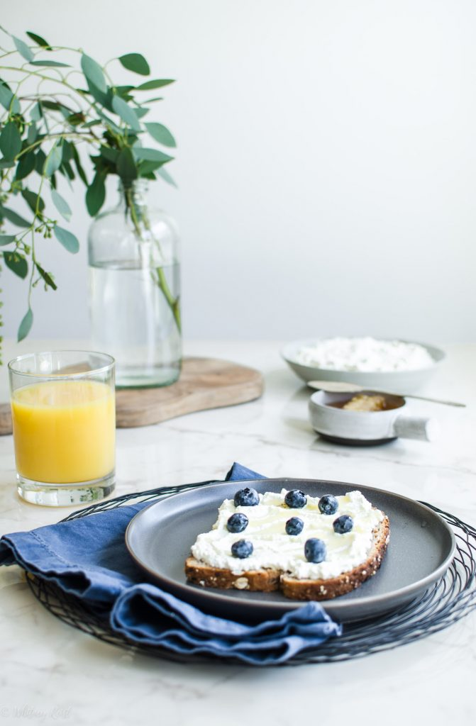 A grey plate with a slice of toast topped with ricotta, honey, and fresh blueberries with a bowl of ricotta in the background.