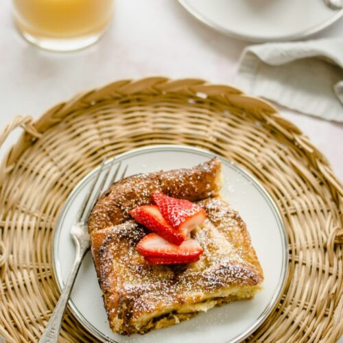 An overhead shot of a plate of ricotta French toast with strawberry syrup with a glass of orange juice on the side.