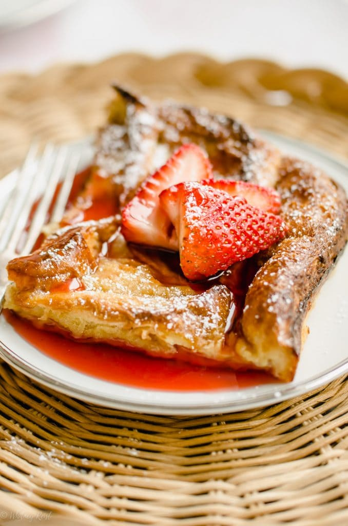A close-up shot of a slice of French toast with strawberry syrup and strawberries on top.