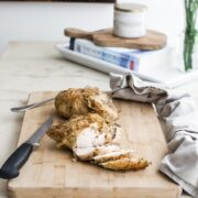 A roasted chicken breast being sliced on a cutting board on a white marble counter top.