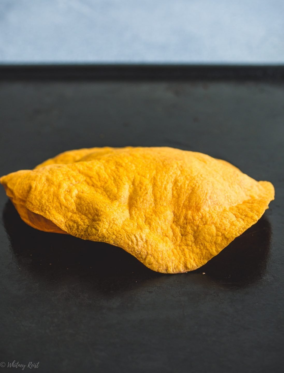 A crispy tortilla on a cooking tray.
