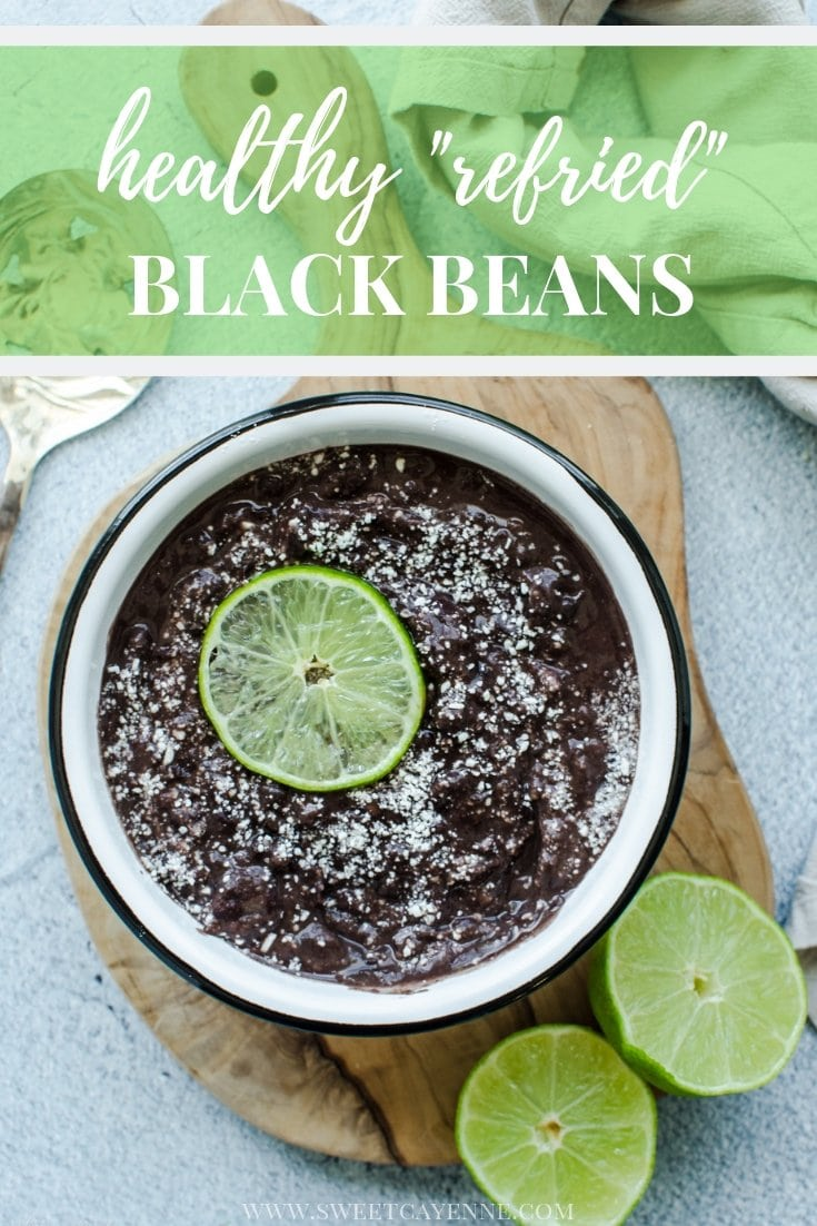 An overhead shot of refried black beans in a white bowl topped with cotijacheese and a lime slice with Pinterest text overlay.
