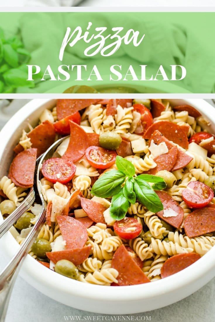 A white bowl filled with pizza pasta salad garnished with fresh basil leaves with Pinterest text overlay.