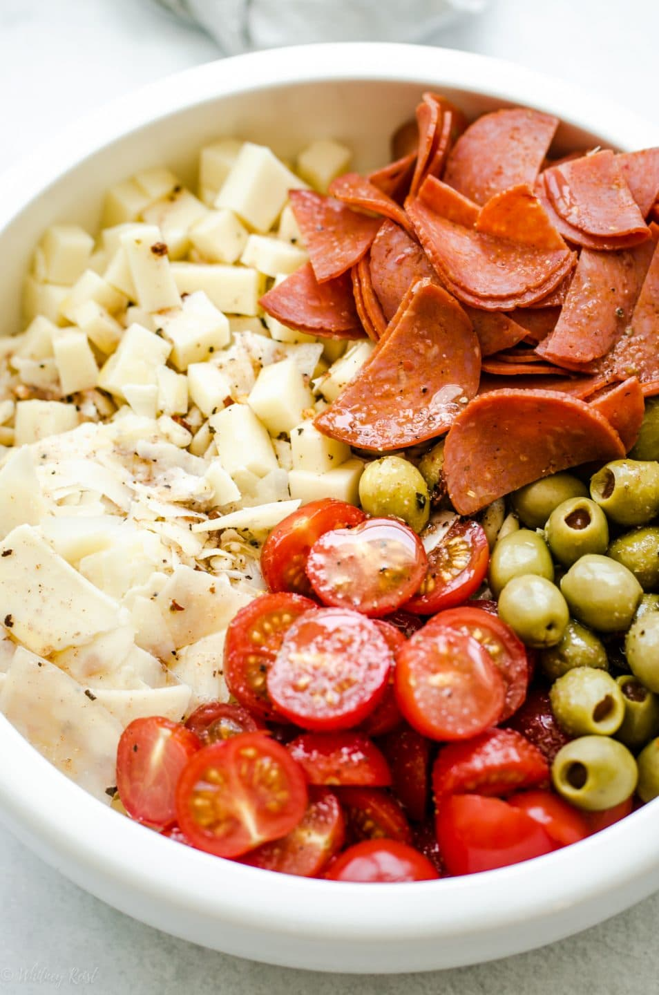 A white bowl filled with ingredients for Pizza Pasta Salad before the salad is tossed.