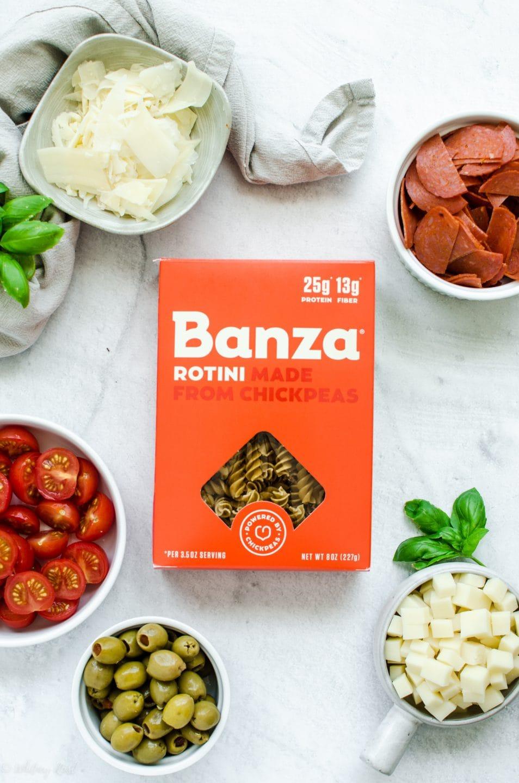 یک جعبه ماکارونی بانزا روی یک بشقاب سفید که با کاسه های سفید از مواد تشکیل دهنده سالاد پاستا پیتزا احاطه شده است.