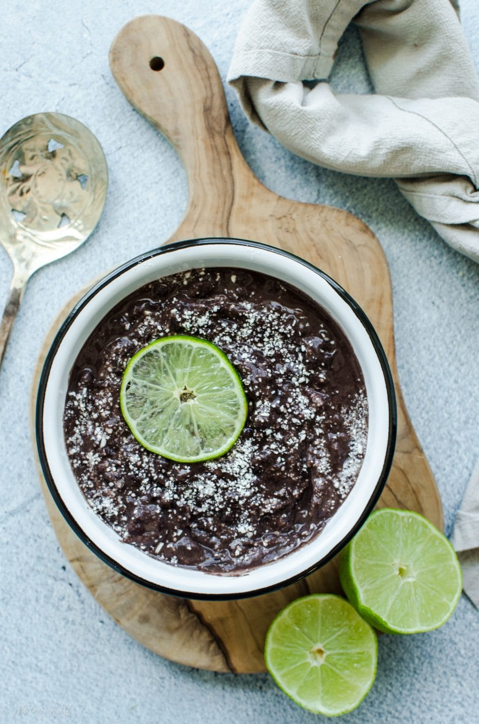 An overhead shot of refried black beans in a white bowl topped with cotija cheese and a lime slice.
