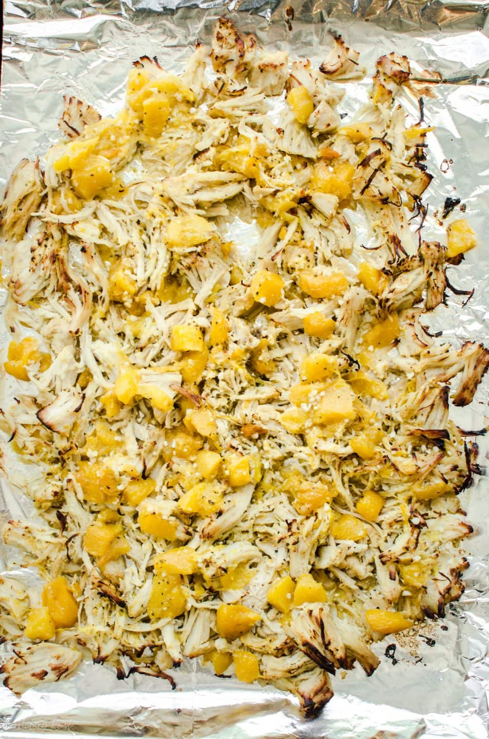 A sheet pan with shredded Mango Mojo Chicken crisped under the broiler.