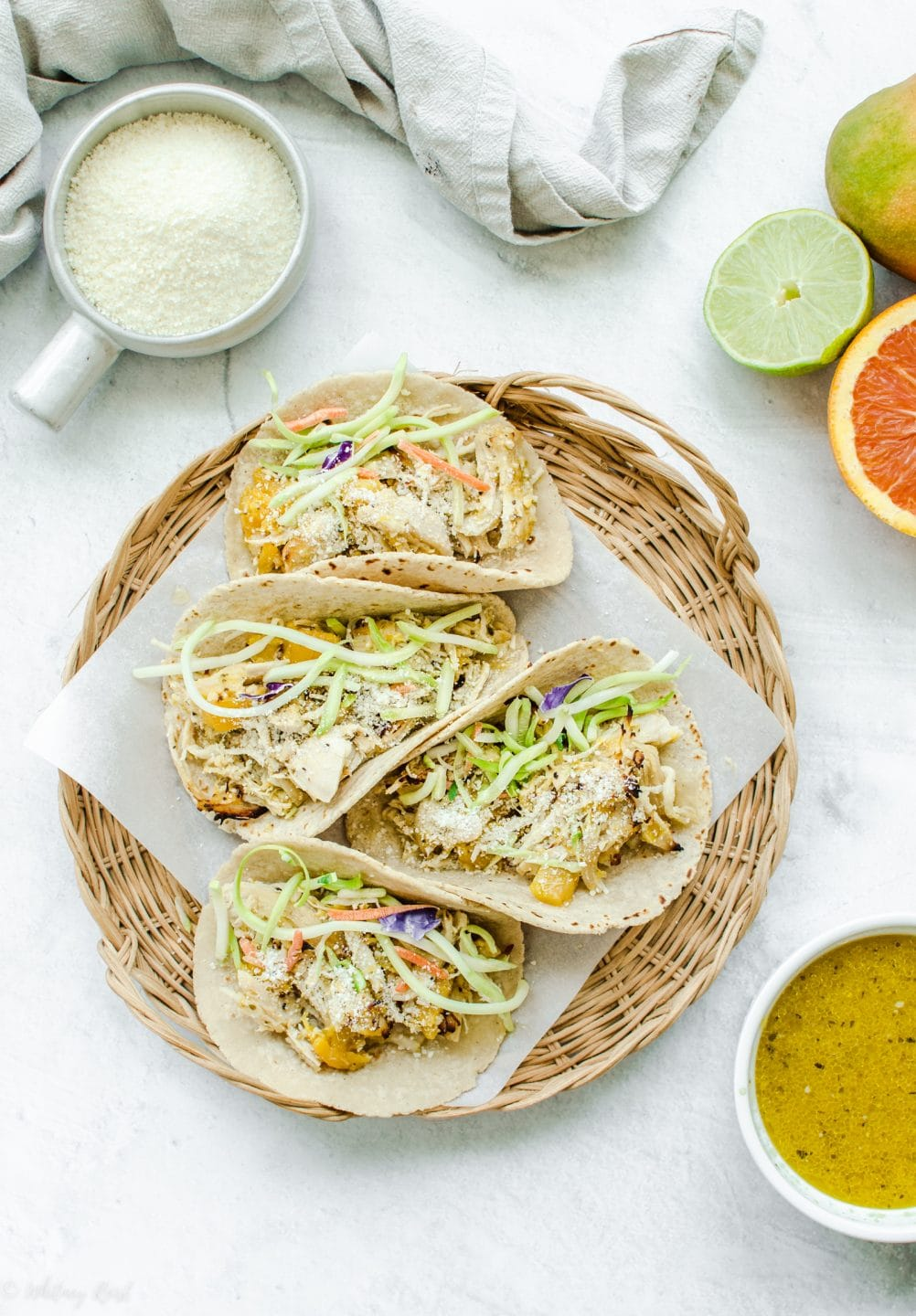 An overhead shot of a wicker charger with parchment paper and Mango Mojo Chicken Tacos with a side of mojo sauce and avocado ranch on the side.