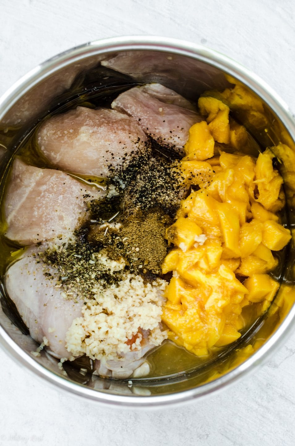 An overhead shot of the inside of an Instant Pot with uncooked chicken breasts, diced mangoes, garlic, and spices.