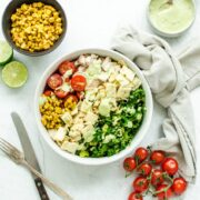 An overhead shot of a white bowl filled with chopped Mexican kale salad with bowls of the ingredients on the side.