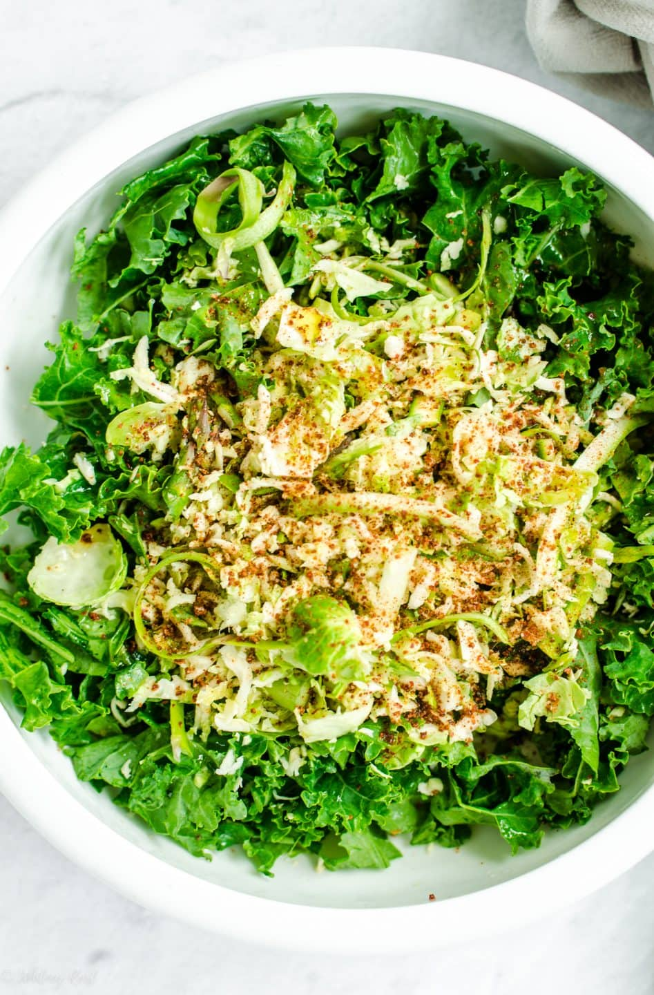 Chopped kale and shaved brussels sprouts in a white bowl.
