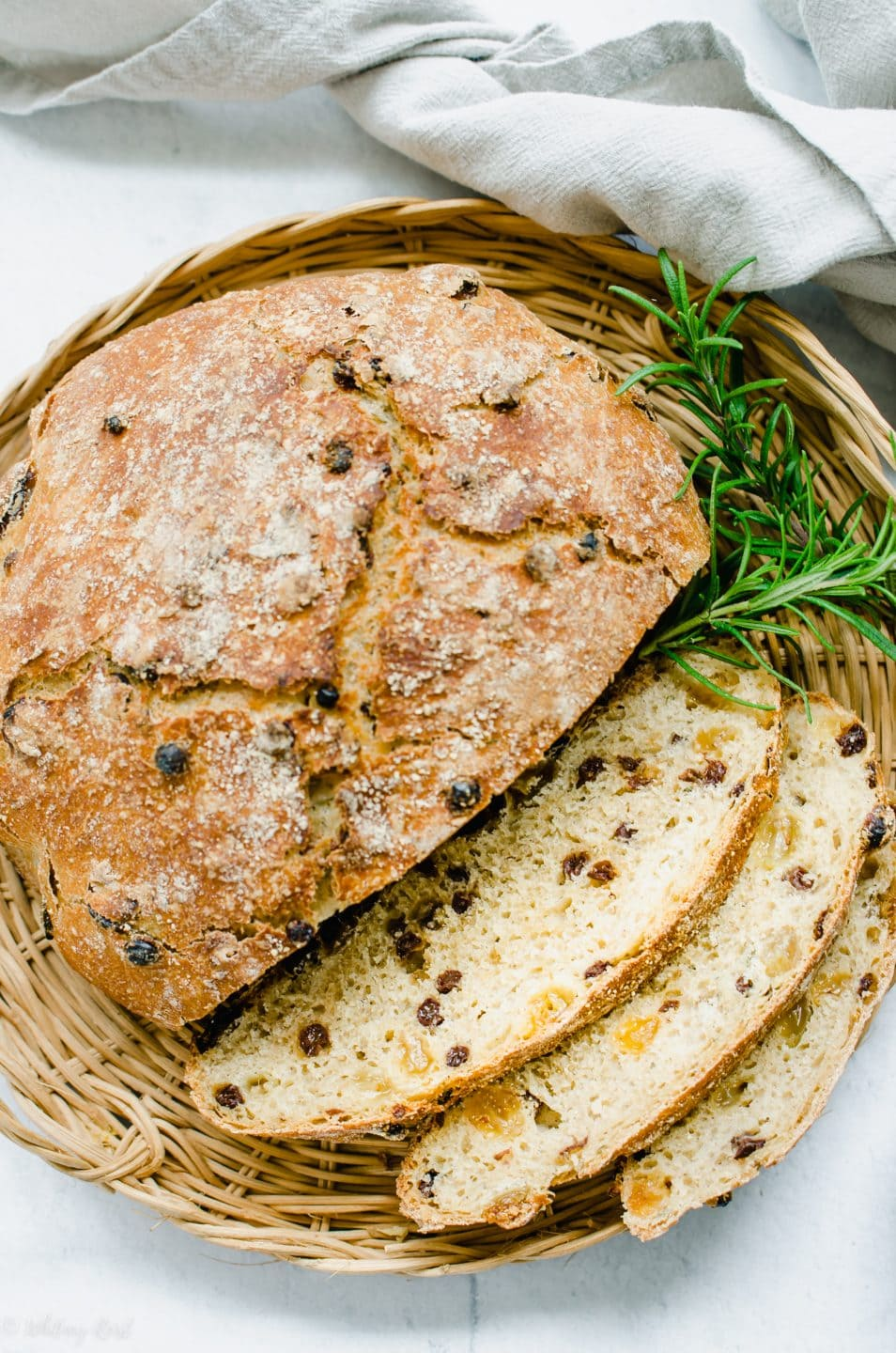 An overhead shot of a loaf of Rosemary Raisin Bread partially sliced on a wicker charger and a sprig of fresh rosemary on the side.