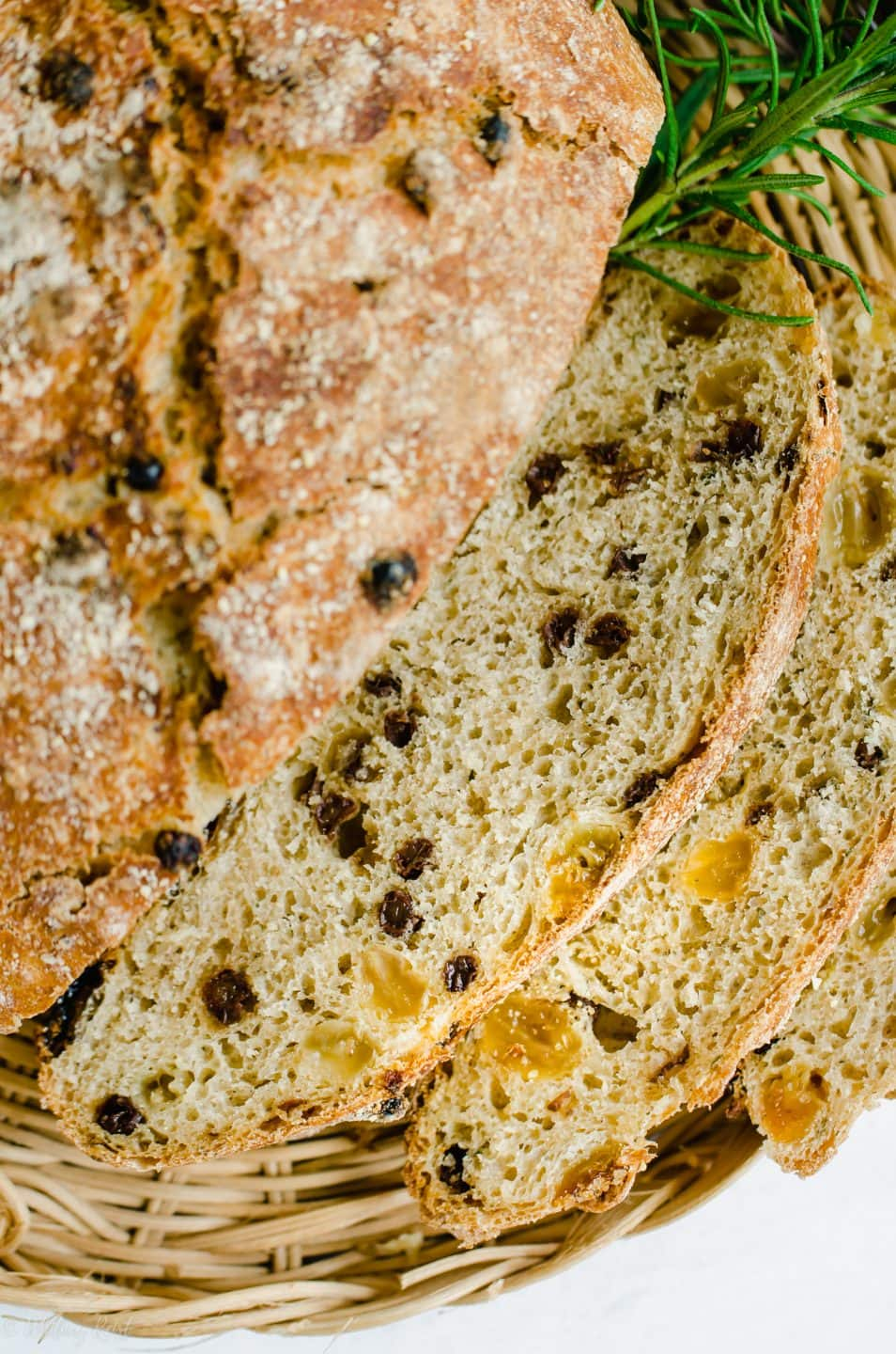A close up shot of slice of Rosemary Raisin Bread to show the texture and holes from fermentation.