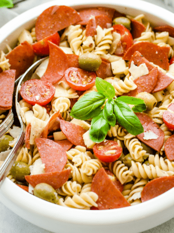 A white bowl filled with pizza pasta salad garnished with fresh basil leaves.