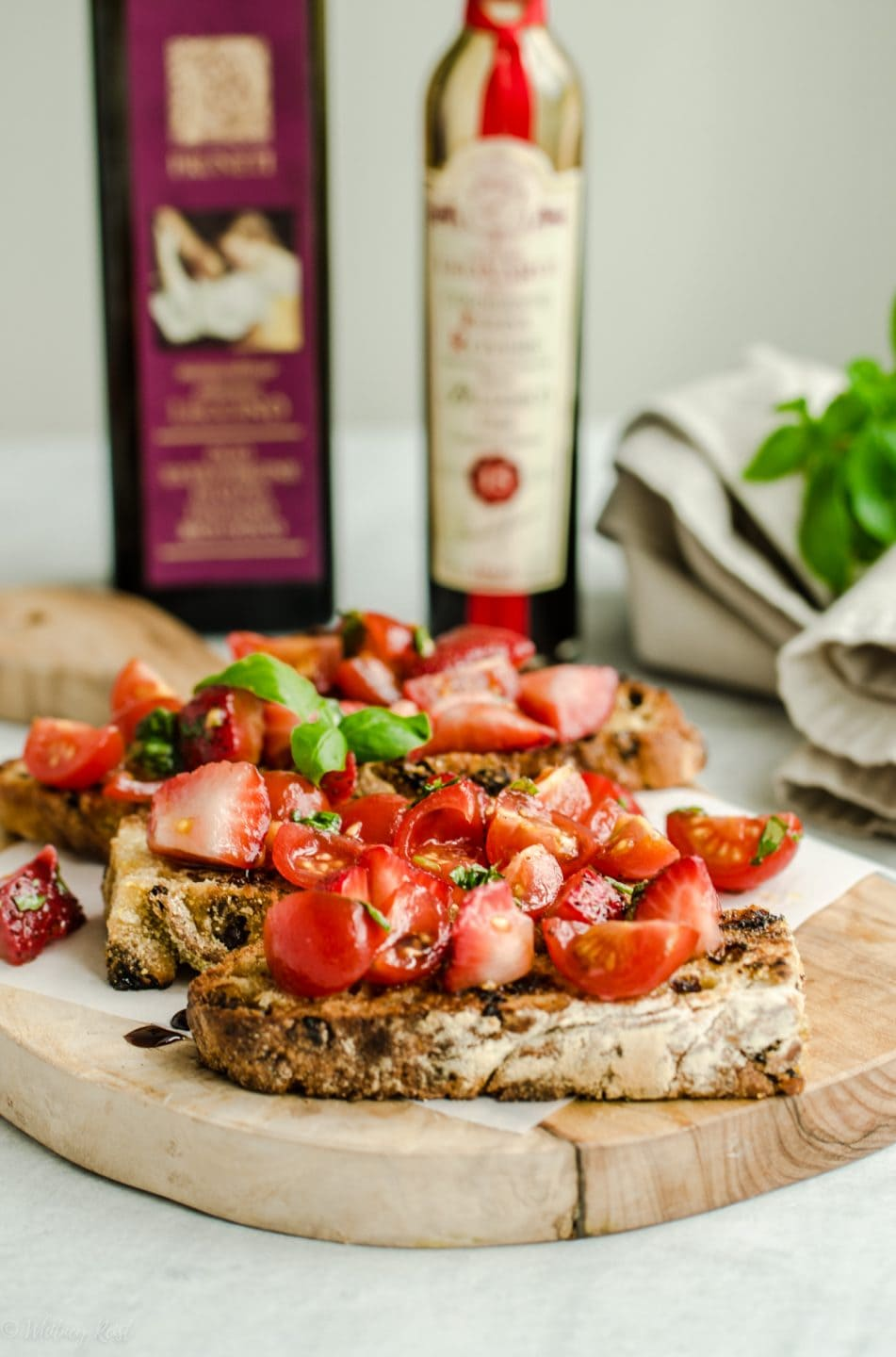 A side shot of strawberry tomato bruschetta on a cutting board with bottles of olive oil and balsamic vinegar in the background.