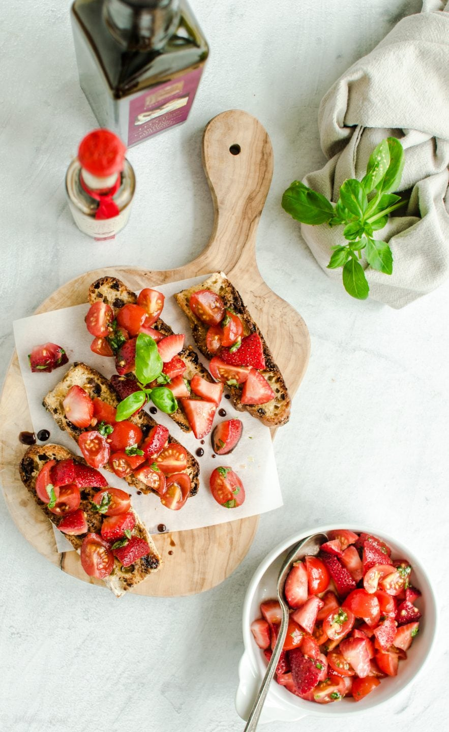 An overhead shot of strawberry bruschetta on parchment paper and a cutting board.