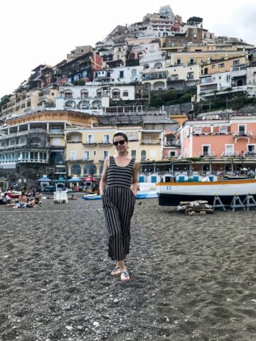 A girl standing on a beach in Positano, Italy.